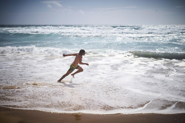Ein junger Mann am Strand von Portugal beim Schaumsurfen